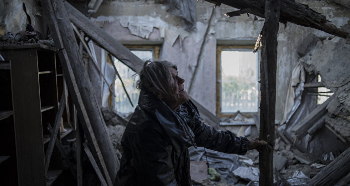 A resident of the village of Staromikhailovka, damaged by a shelling, in the Donetsk region.