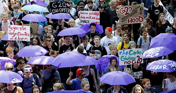 People hold banners and umbrellas as they walk during the protest demonstration at the G20 summit in Hamburg, Germany, July 7, 2017
