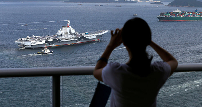 An onlooker takes a photo as China's aircraft carrier Liaoning sails into Hong Kong, China July 7, 2017