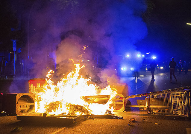 Policemen by a burning barricade in the so-called Schanzenviertel area of Hamburg during the G20 summit, on the morning of 9 July 2017