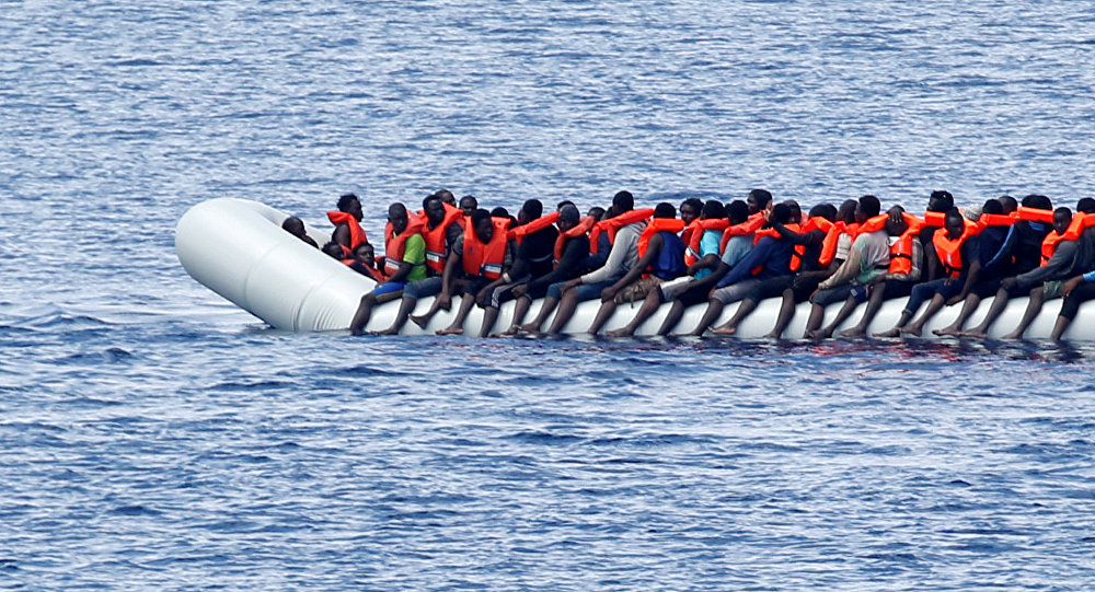 Migrants wait to be rescued by Save the Children NGO crew in the Mediterranean sea off Libya coast, June 18, 2017.