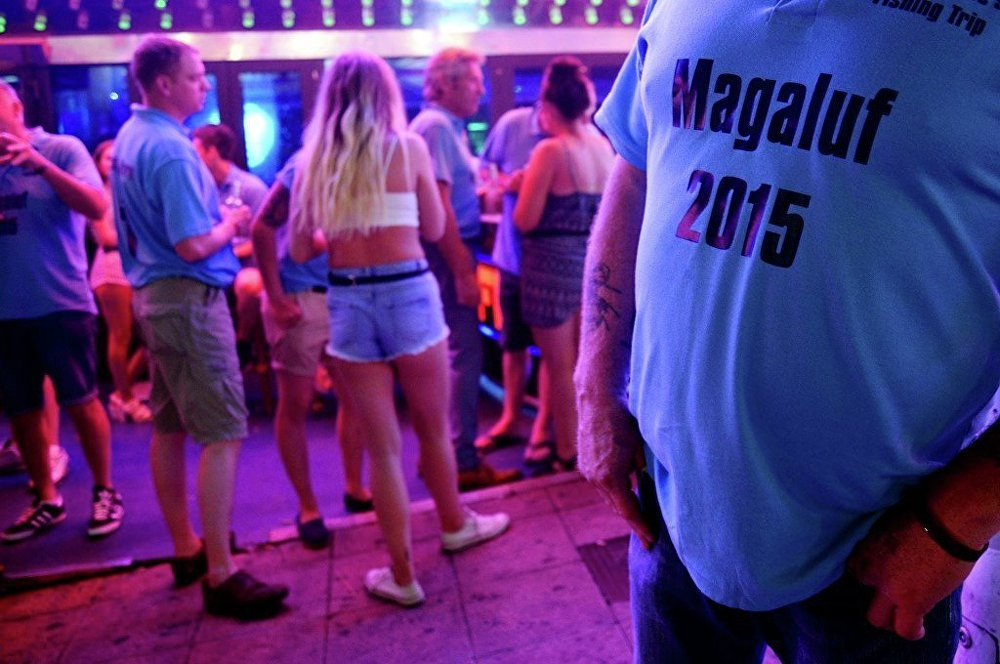 Tourists stand on the street at the resort of Magaluf, in Calvia town, on the Spanish Balearic island of Mallorca, Wednesday, June 10, 2015.