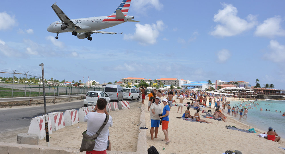A plane lands at the Princess Juliana International Airport as beachgoers watch in Philipsburg, St. Maarten, a Dutch Caribbean territory, Thursday, July 13, 2017. On Wednesday, a New Zealand tourist was killed by the blast from a jetliner taking off when she was knocked into a wall as she tried to cling to a fence to feel the blast.