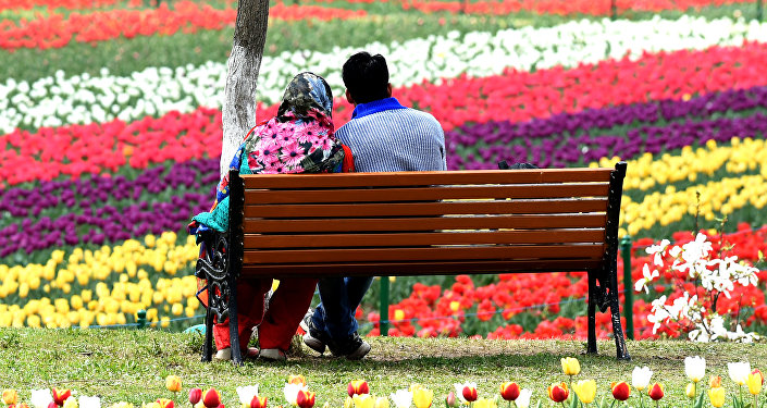 An Indian Kashmiri couple sits on a bench at a Tulip Garden, claimed to be Asia's largest, in Srinagar on April 1, 2017