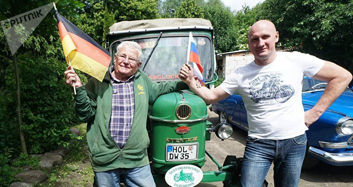 Retired Winfried Langner, left, drives a tractor from Germany to Russia. He made a pit stop in Kaliningrad en route from Lower Saxony to St. Petersburg
