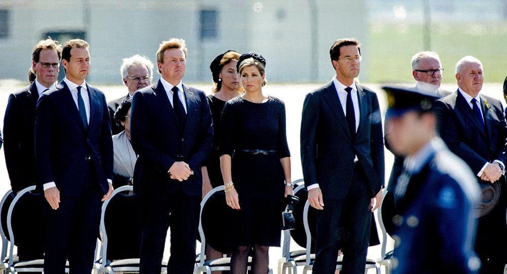 (From L) Minister Lodewijk Asscher, King Willem-Alexander and Queen Maxima of The Netherlands, and Dutch Prime minister Mark Rutte hold a minute's silence as they attend a ceremony upon the arrivals of a plane from Ukraine, carrying the remains of victims of downed Malaysia Airlines flight MH17, at Eindhoven Airbase on July 23, 2014