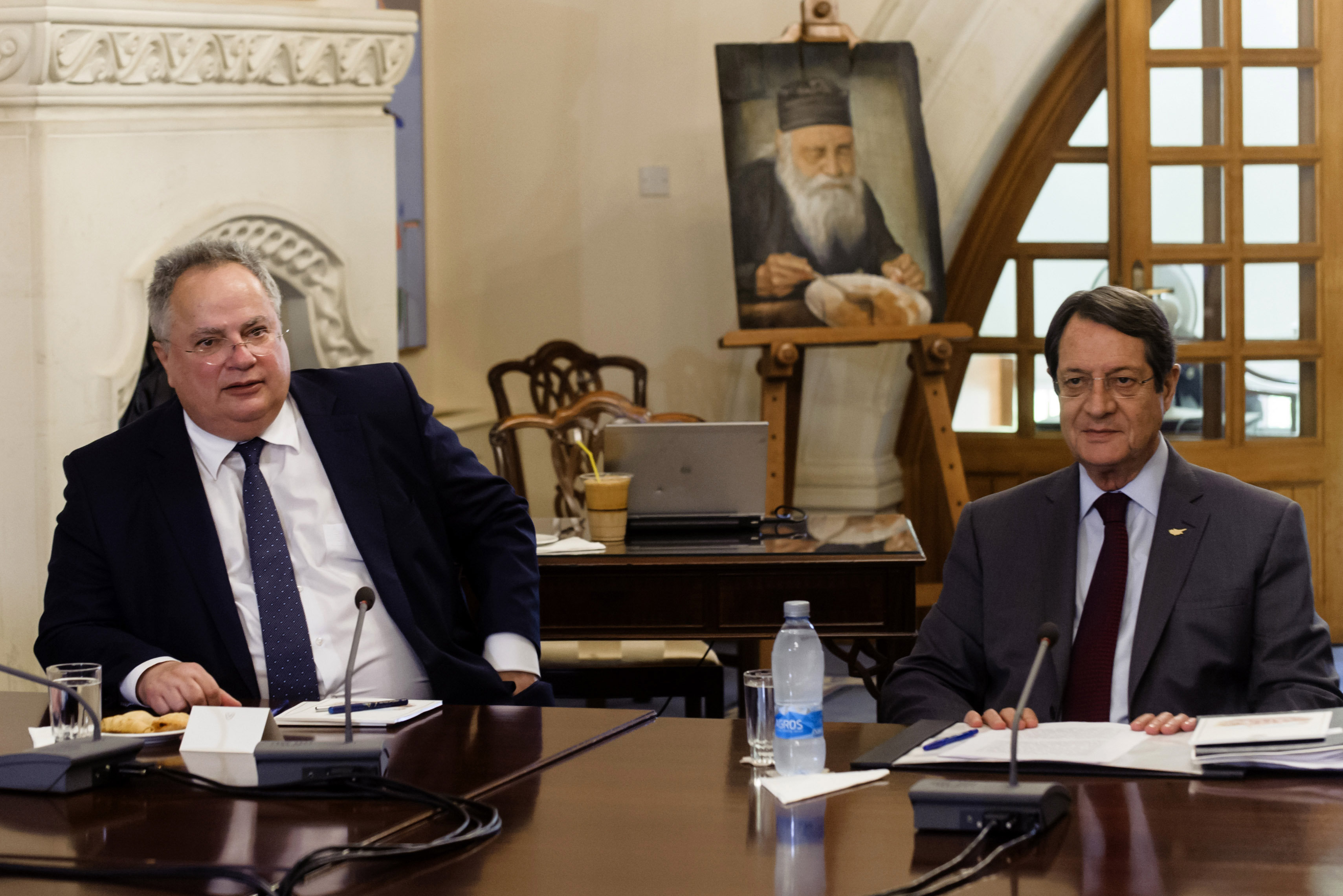 Greek Foreign Minister Nikos Kotzias (L) sits next to Cypriot President Nicos Anastasiades (R) on July 18, 2017 in the presidential palace in Nicosia during a national council meeting of Greek Cypriot party political leaders. The foreign ministers of Greece and Turkey are in Cyprus on separate missions to review the way forward after UN-backed reunification talks collapsed in Switzerland earlier this month. Turkish Foreign Minister Mevlut Cavusoglu is to hold talks in breakaway northern Cyprus, Ankara announced.