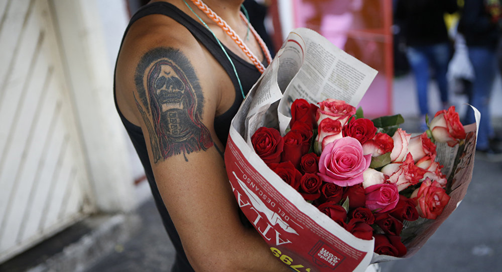 A tattooed devotee of La Santa Muerte, or Saint Death, sells flowers to devotees paying Day of the Dead visits to a well-known Santa Muerte altar in Tepito, Mexico City, Wednesday, Nov. 2, 2016