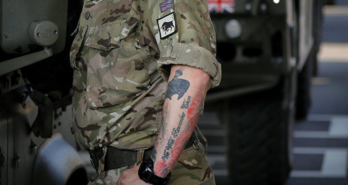 A British serviceman, his arm tattooed with poppies that reads We Will Remember Them stands near vehicles in the Romanian border checkpoint in Giurgiu, Romania, Thursday, June 1, 2017 to take part in the alliance's Noble Jump 2017 exercise which tests the readiness of alliance troops.
