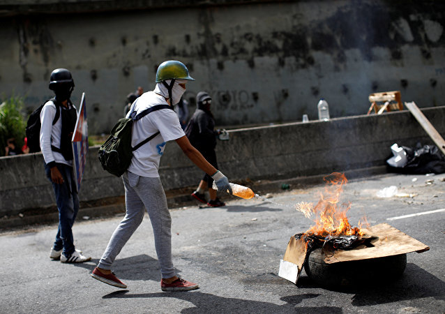 A demonstrator sets a roadblock on fire during a strike called to protest against Venezuelan President Nicolas Maduro's government in Caracas, Venezuela July 26, 2017.