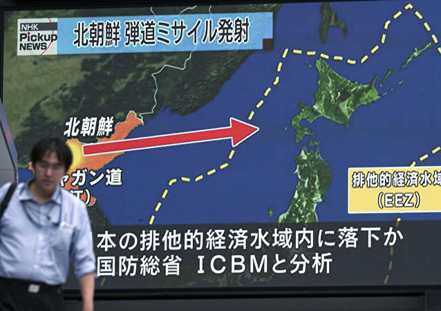 A man walks in front of a public TV screen broadcasting news of North Korea's test-firing of its second intercontinental ballistic missile, in Tokyo Saturday, July 29, 2017.