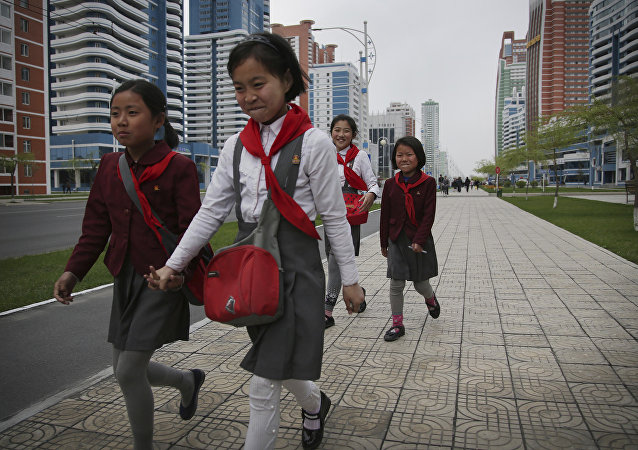 North Korean school girls hold back their laughter at seeing their photograph being taken while walking along Mirae Scientists Street on Wednesday, April 19, 2017, in Pyongyang, North Korea