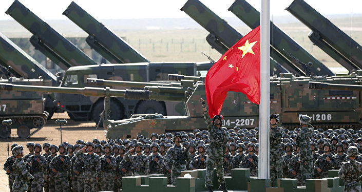 In this photo released by China's Xinhua News Agency, Chinese People's Liberation Army (PLA) troops perform a flag raising ceremony Sunday, July 30, 2017 for a military parade to commemorate the 90th anniversary of the founding of the PLA on Aug. 1 at Zhurihe training base in north China's Inner Mongolia Autonomous Region