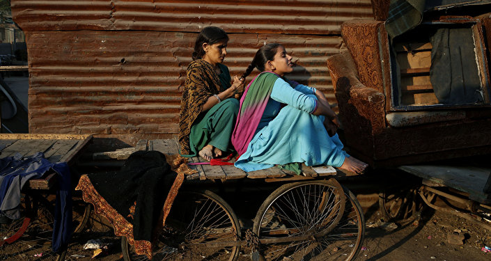 A woman ties the hair of her daughter into a braid as they sit on a cart before evening sets in at a poor neighborhood in New Delhi, India, Thursday, Dec. 5, 2013