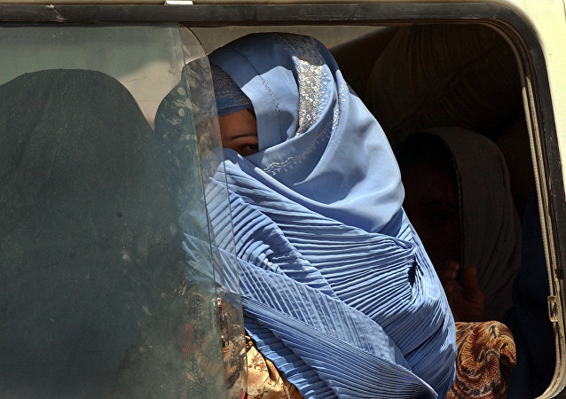 Woman clad in burka peeps from the window of a bus (File)