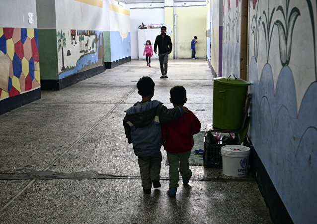 Children walk through a former industrial warehouse at the Oinofyta refugee camp, some 60 km north of Athens, on March 13, 2017 in Oinofyta
