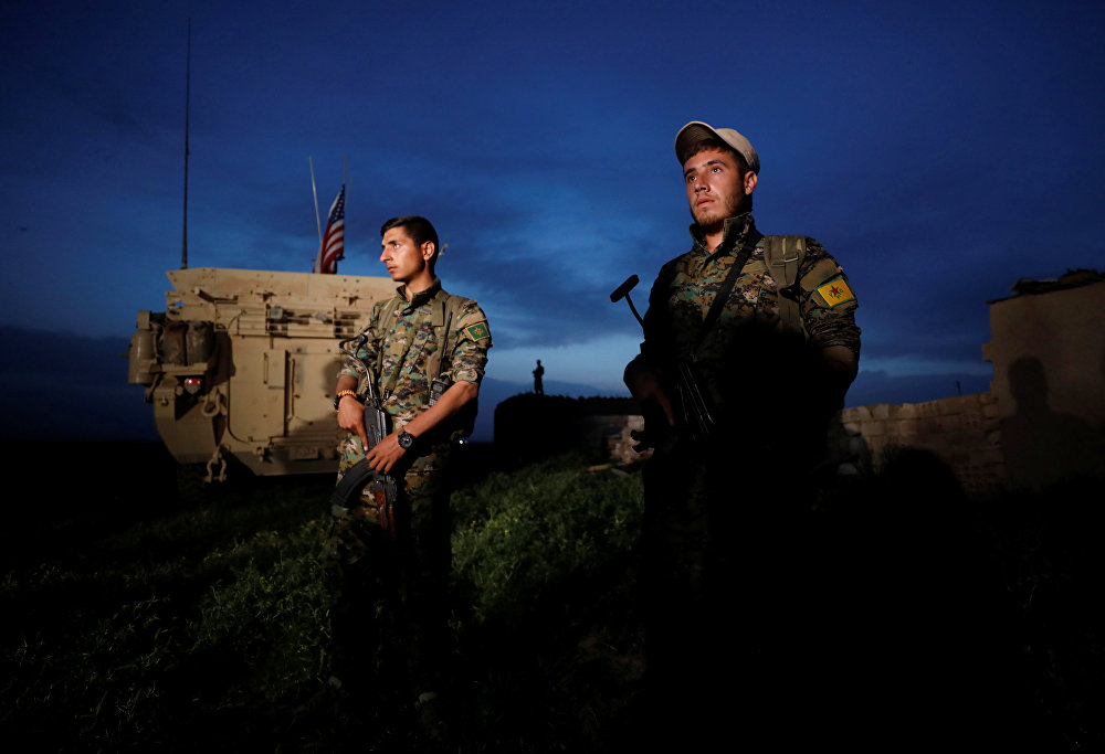 Kurdish fighters from the People's Protection Units (YPG) stand near a US military vehicle in the town of Darbasiya next to the Turkish border, Syria April 28, 2017.