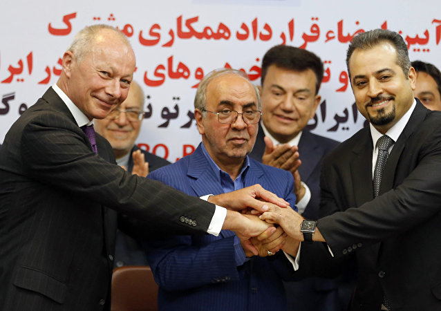 (L to R) Thierry Bollore, deputy director of Competitiveness at Renault, Mansour Moazami, Chairman of the Board of Directors of IDRO Group, and Kourosh Morshed Solouk, deputy director of the Iranian Automobile Importers Association, shake hands as they attend a signing of a deal ceremony in Tehran on August 7, 2017