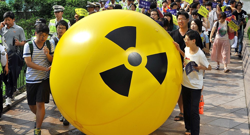 South Korean activists march while rolling a large balloon with a radioactivity warning.