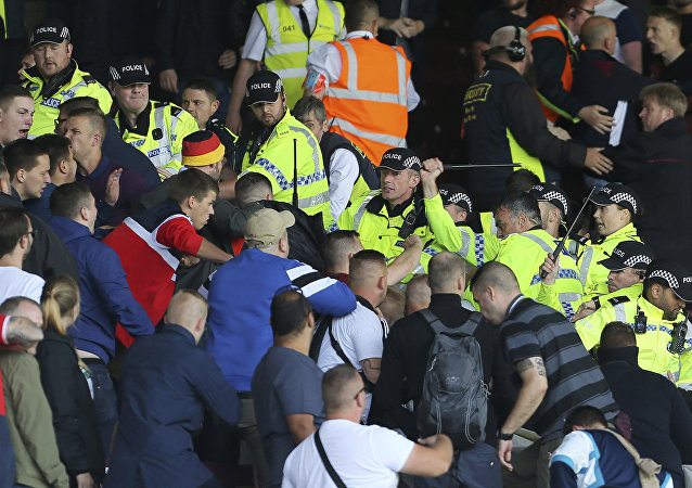British police confront Hannover soccer club fans during the game against Burnley during their pre-season friendly match at Turf Moor, Burnley, Saturday Aug. 5, 2017. Burnley's pre-season friendly with German side Hannover was abandoned due to crowd trouble.