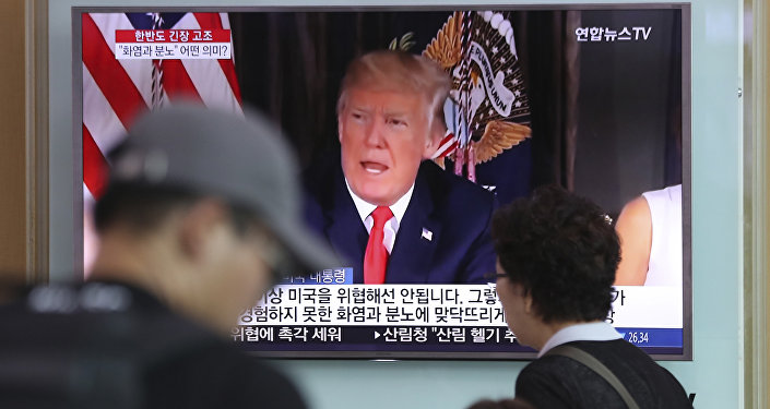 People walk by a TV screen showing a local news program reporting with an image of U.S. President Donald Trump at the Seoul Train Station in Seoul, South Korea, Wednesday, Aug. 9, 2017