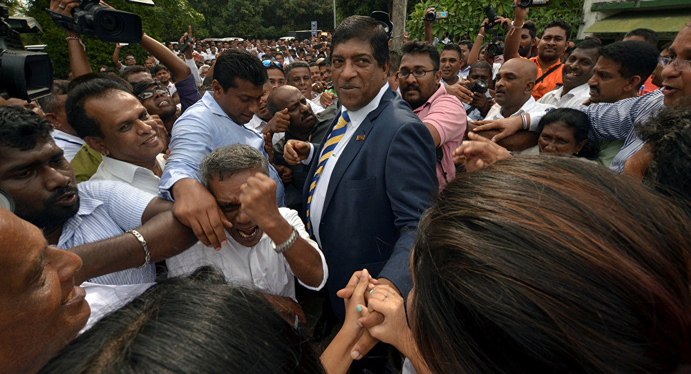 Sri Lanka's foreign minister Ravi Karunanayake reacts as he is surrounded by his supporters after he resigned on Thursday over corruption charges in Colombo Sri Lanka