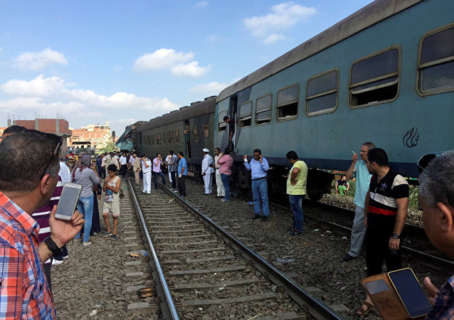 Egyptians look at the crash of two trains that collided near the Khorshid station in Egypt's coastal city of Alexandria, Egypt
