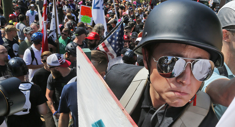 A white nationalist demonstrator with a helmet and shield walks into Lee Park in Charlottesville, Va., Saturday, Aug. 12, 2017. Hundreds of people chanted, threw punches, hurled water bottles and unleashed chemical sprays on each other Saturday after violence erupted at a white nationalist rally in Virginia.