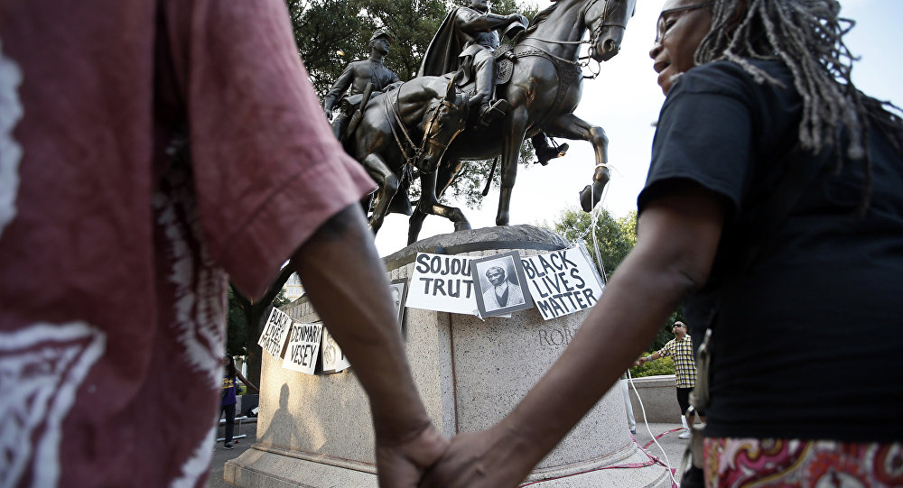 Activists gather around the Confederate Army Gen. Robert E. Lee statute at Lee Park chanting the names of Civil War era activists in Dallas. Gen. Robert E. Lee was vilified during the Civil War only to become a heroic symbol of The Lost Cause and eventually a racist icon.