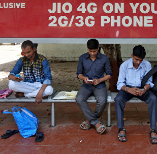 Commuters use their mobile phones as they wait at a bus stop with an advertisement of Reliance Industries' Jio telecoms unit, in Mumbai, India July 10, 2017