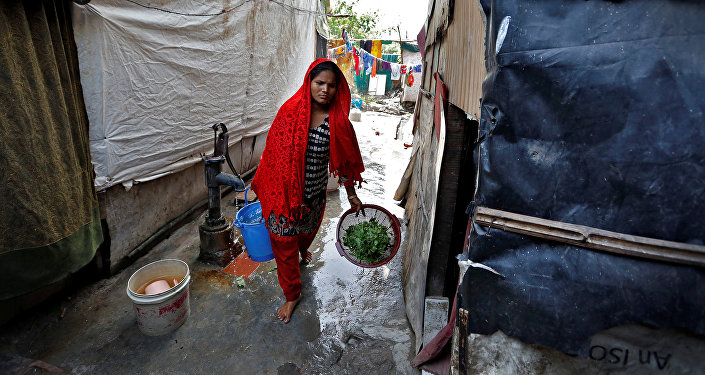 A woman from the Rohingya community carries vegetables in a camp in Delhi, August 17, 2017