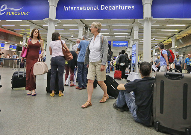 In this Thursday, July 2, 2015 file photo, people queue as they wait at the St. Pancras international train station terminal in London