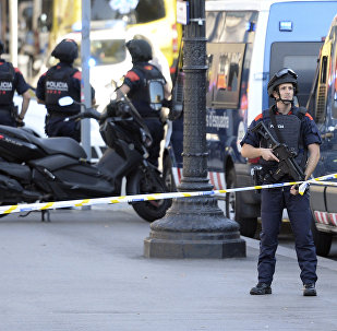 Armed policemen stand in a cordoned off area after a van ploughed into the crowd, injuring several persons on the Rambla in Barcelona on August 17, 2017
