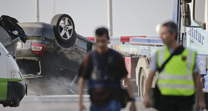 Police officers walk near an overturned car onto a platform at the spot where terrorists were intercepted by police in Cambrils, Spain, Friday, Aug. 18, 2017