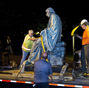 Workers strap down the monument dedicated to U.S. Supreme Court Chief Justice Roger Brooke Taney on a flatbed truck after it was removed from outside the Maryland State House in Annapolis, Md., early Friday, Aug. 18, 2017