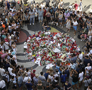 People gather at a memorial tribute of flowers, messages and candles to the victims on Barcelona's historic Las Ramblas promenade on the Joan Miro mosaic, embedded in the pavement where the van stopped after killing at least 13 people in Barcelona , Spain, Friday, Aug. 18, 2017