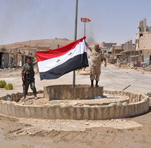 Pro-government fighters hold up a Syrian flag in the central Syrian town of Al-Sukhnah
