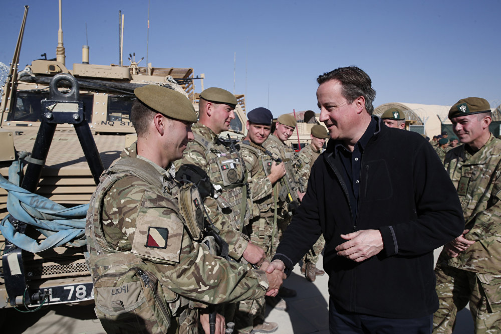 Then Britain's Prime Minister David Cameron, right, talks to British soldiers at Camp Bastion, outside Lashkar Gah, the provincial capital of Helmand province in southern Afghanistan, Monday, Dec. 16, 2013.