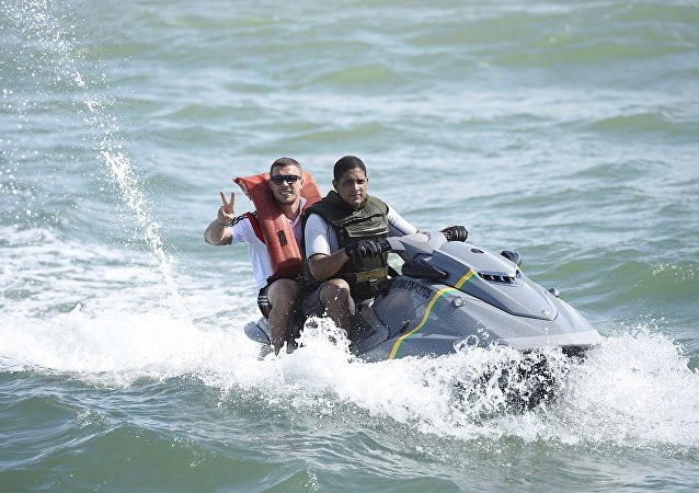 In this June 10, 2014 photo released by the German Football federation, DFB, former German national soccer player Lukas Podolski, left, rides on a jet-ski off Santo Andre, Brazil.
