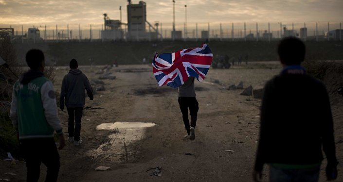 In this Tuesday, Oct. 25, 2016 file photo a man runs with a British flag inside a makeshift camp known as the jungle near Calais, northern France