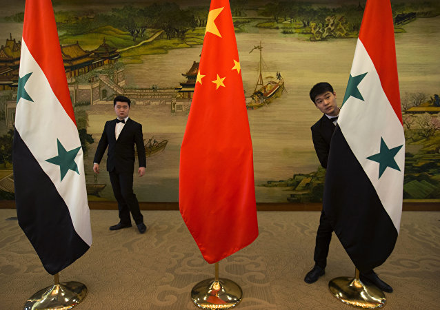 Attendants adjust Syrian and Chinese flags before a briefing at China's Ministry of Foreign Affairs in Beijing, Thursday, Dec. 24, 2015
