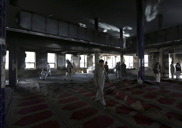 Afghan men are seen inside a Shiite mosque where gunmen attacked during Friday prayers, in Kabul, Afghanistan, Saturday, Aug. 26, 2017