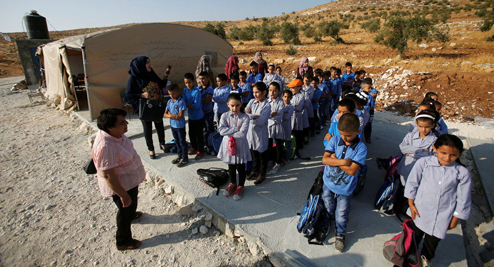 Palestinian schoolchildren queue outside a tent where they attend lessons after Israeli troops confiscated caravans used as school classrooms, due to the lack of an Israeli-issued construction permit, in the West Bank village of Jubbet Al Dhib, near Bethlehem August 24, 2017