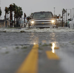 A truck drives moves through flood waters left behind by Hurricane Harvey, Saturday, Aug. 26, 2017, in Aransas Pass, Texas.