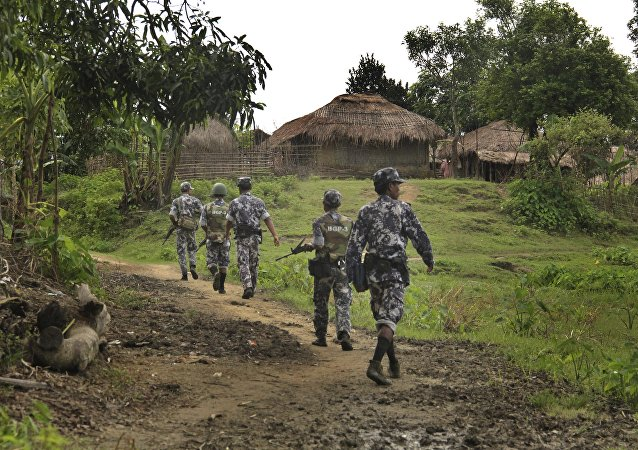In this Friday, July 14, 2017 photo, Myanmar Border Guard Police (BGP) officers walk along a path ahead of journalists in Tin May village, in which Myanmar government and military claim the existence of Muslim terrorists in Buthidaung, Rakhine State, Myanmar.
