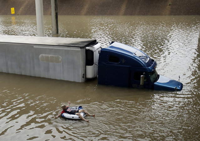A man floats past a truck submerged on a freeway flooded by Tropical Storm Harvey on Sunday, Aug. 27, 2017, near downtown Houston.