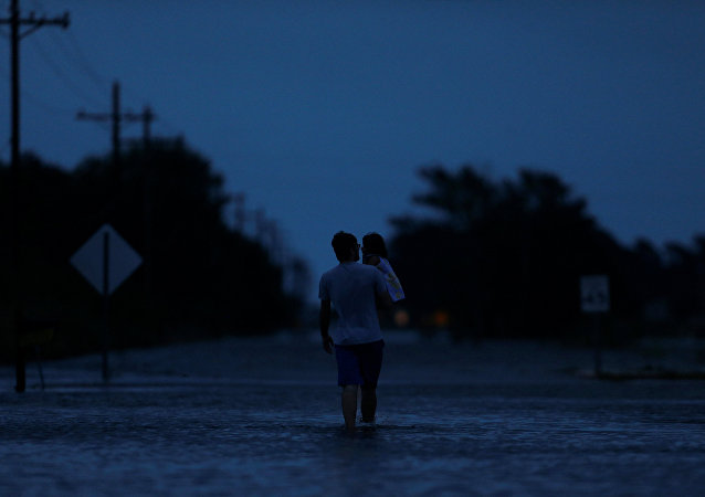 Ethan holds his 2-year-old daughter Zella as they walk through flood waters from Tropical Storm Harvey in Iowa, Calcasieu Parish, Louisiana, US.