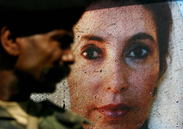A portrait of Benazir Bhutto on the side of her open-air vehicle is splattered with bomb residue, as it is guarded by a Pakistani soldier in Karachi, Pakistan, on Friday Oct. 19, 2007, following an assassination attempt on Thursday.