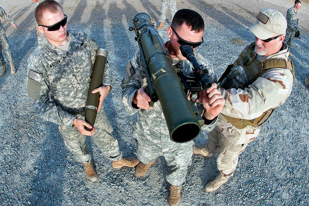 A civilian instructor coaches two paratroopers on how to use a Carl Gustav M3 84mm recoilless rifle during a certification course on Fort Bragg, N.C., Dec. 6, 2011