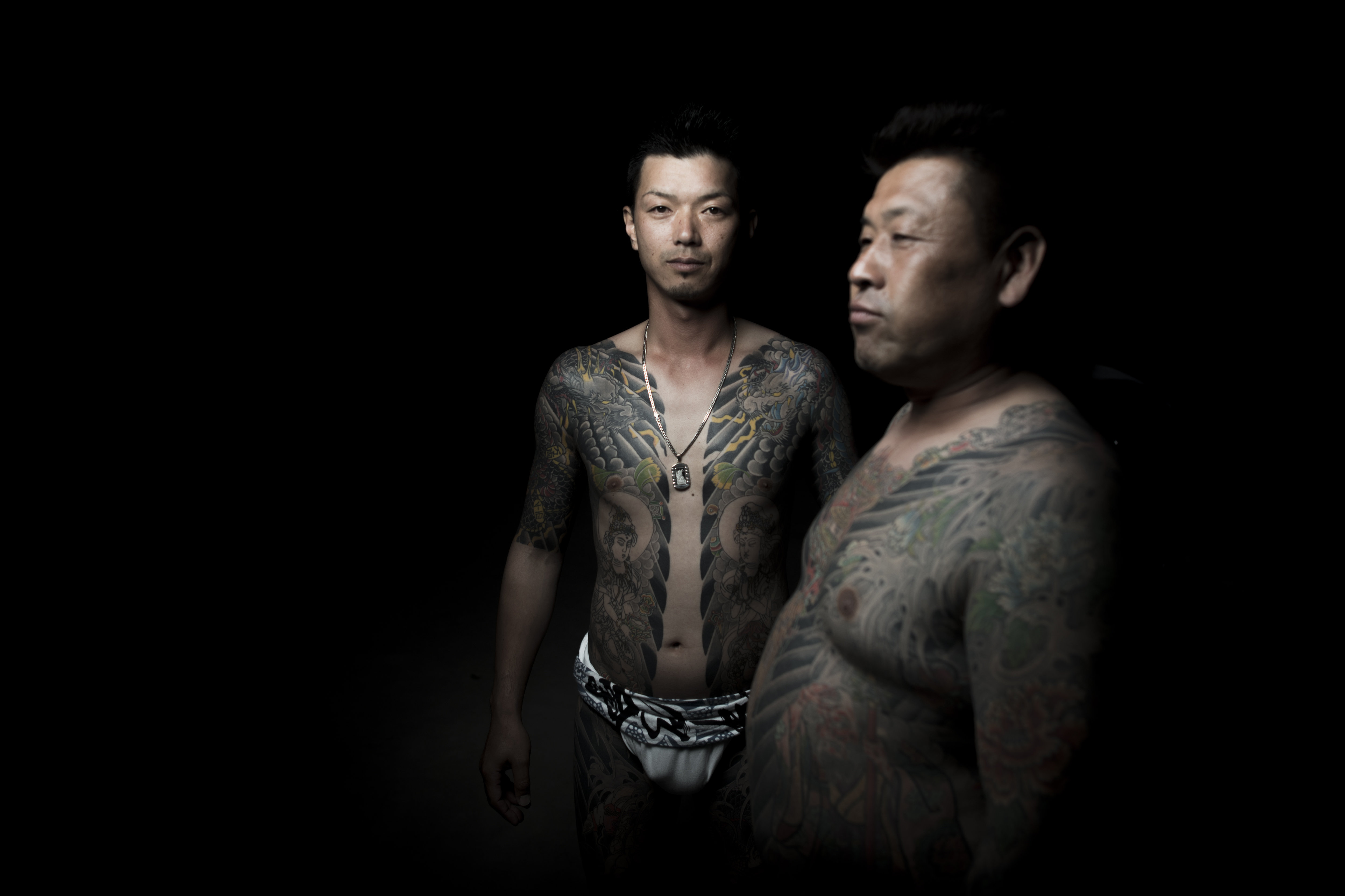 In this picture taken on May 20, 2017, men pose for photographs showing their Irezumi Japanese traditional tattoos related to the Yakuza's universe, during the Sanja Matsuri festival in Tokyo